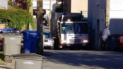 A city garbage truck trying to squeeze into a Fairview alley off Hemlock Street.