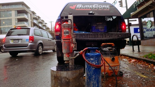 A coring machine waits in the cold rain. The operator waits in the warm truck.