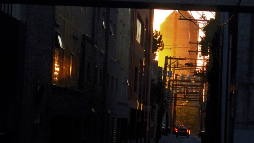 Looking east down an alley, under a walkway, as through a door, at a golden sunrise at 7 a.m.