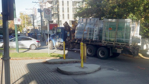 A large truck bearing window sections opts to clip the trees rather than the newly refurbished bike island.