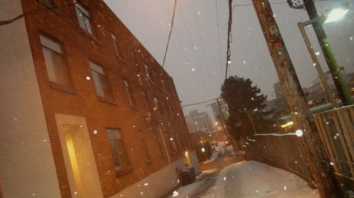 The falling snow at 7:35 a.m. is accumulating in the alley but not on busy Hemlock St.